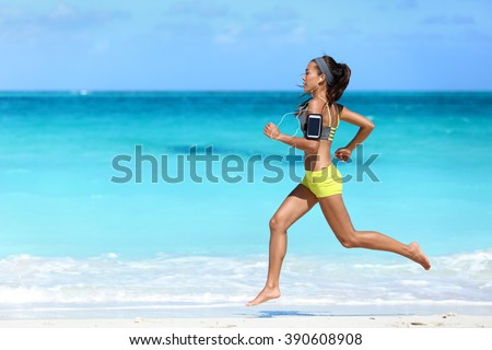 Fitness runner woman running on beach listening to music motivation with phone case sport armband strap. Sporty athlete training cardio barefoot with determination under summer sun. - stock photo