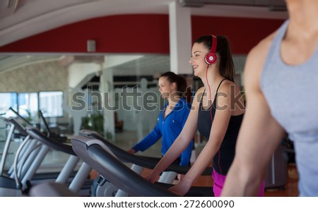 Fitness running people. Sports people running on the treadmill at the gym. Athletes wearing sportswear and running in the gym a rear. - stock photo