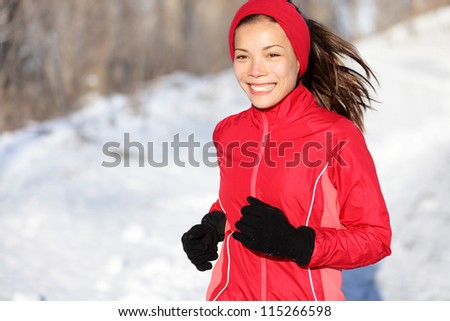 Fitness running woman in winter. Runner closeup of happy active sport model jogging in snow in winter forest. Beautiful mixed race asian chinese caucasian female model. - stock photo