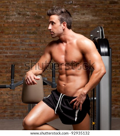 fitness shaped muscle man posing on dark gym