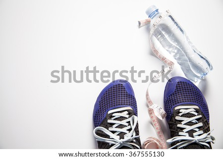 fitness shoes with measuring tape and water bottle - stock photo