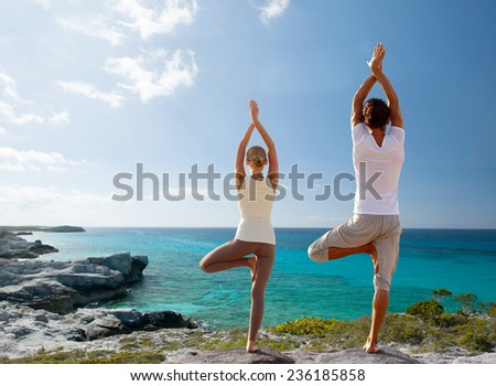 fitness, sport, and lifestyle concept - couple making yoga exercises on beach from back - stock photo