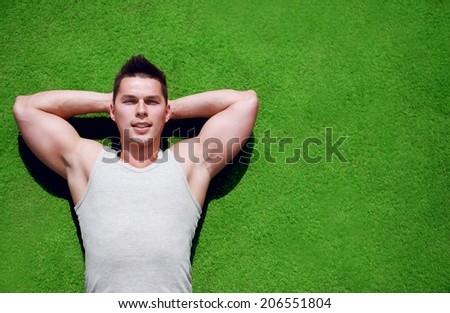 Fitness, sport and vacation concept - handsome man relaxing on the grass in summer day, copy space