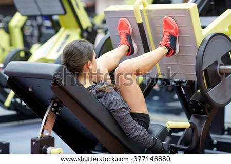fitness, sport, bodybuilding, exercising and people concept - young woman flexing muscles on leg press machine in gym - stock photo
