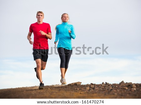 Fitness sport couple jogging outside, training together outdoors. Running on nature trail - stock photo