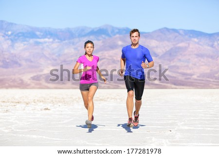 Fitness sport couple running jogging outside on trail in desert landscape. - stock photo