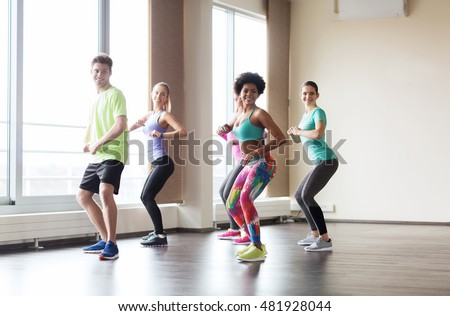 fitness, sport, dance and healthy lifestyle concept - group of smiling people with coach dancing in gym or studio