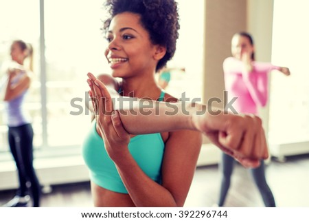 fitness, sport, dance, people  and lifestyle concept - close up of smiling african american woman with group of women dancing zumba in gym or studio - stock photo