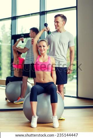 fitness, sport, exercising and diet concept - smiling young woman and personal trainer with dumbbell in gym