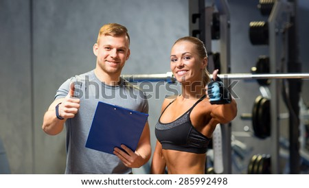 fitness, sport, exercising and diet concept - smiling young woman and personal trainer with clipboard showing thumbs up in gym - stock photo