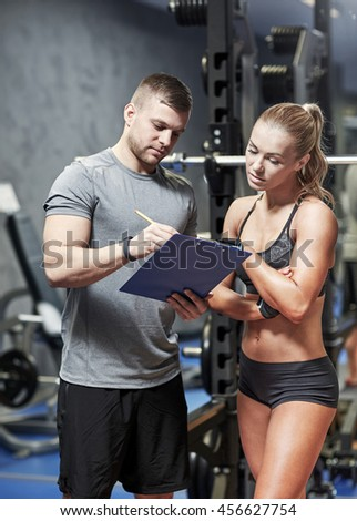 fitness, sport, exercising and diet concept - young woman and personal trainer with clipboard writing exercise plan in gym - stock photo
