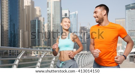 fitness, sport, exercising and healthy lifestyle concept - smiling couple running or jogging over dubai city street background - stock photo