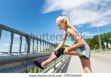 fitness, sport, exercising and healthy lifestyle concept - young woman with injured knee or leg outdoors - stock photo