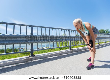 fitness, sport, exercising and healthy lifestyle concept - young woman with knee support brace injured leg outdoors - stock photo