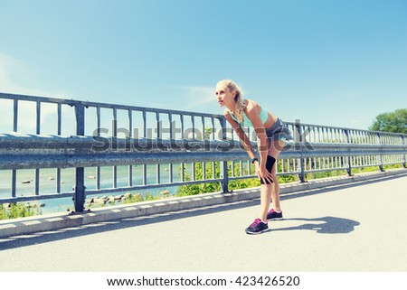 fitness, sport, exercising and healthy lifestyle concept - young woman with knee support brace on leg outdoors - stock photo