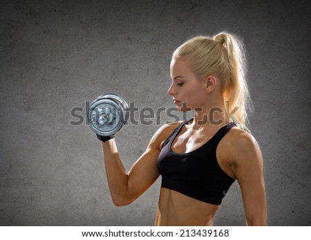 fitness, sport, exercising and people concept - sporty woman with heavy steel dumbbells over concrete wall background