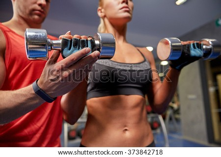 fitness, sport, exercising and weightlifting concept - young woman and personal trainer with dumbbells flexing muscles in gym - stock photo