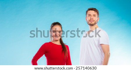 Fitness, sport, exercising concept Portrait of sporty young happy couple man and woman on blue background - stock photo