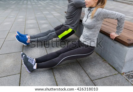 fitness, sport, exercising, training and people concept - couple doing triceps dip exercise on city street bench - stock photo
