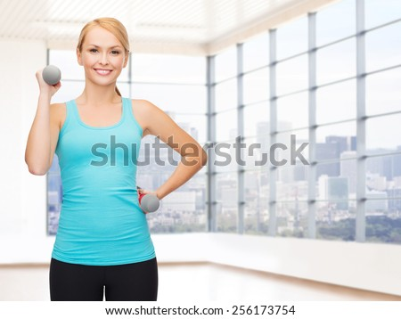 fitness, sport, fitness and people concept - smiling woman with light weight dumbbells flexing biceps over gym or home background - stock photo