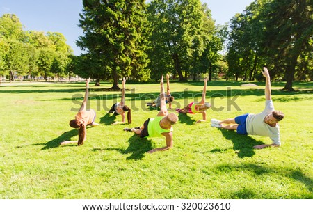 fitness, sport, friendship and healthy lifestyle concept - group of happy teenage friends exercising at boot camp - stock photo