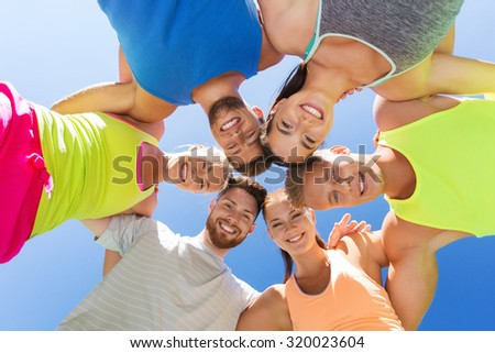 fitness, sport, friendship and healthy lifestyle concept - group of happy teenage friends in circle outdoors - stock photo