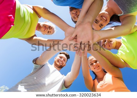 fitness, sport, friendship and healthy lifestyle concept - group of happy teenage friends with hands on top outdoors - stock photo