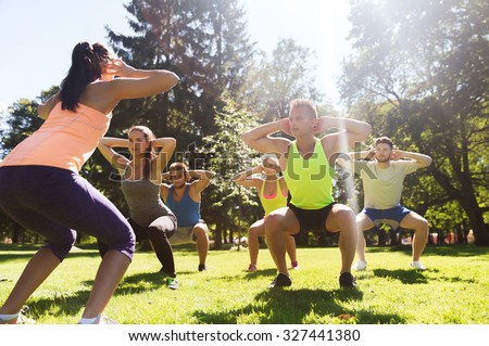 fitness, sport, friendship and healthy lifestyle concept - group of teenage friends or sportsmen exercising and doing squats at boot camp - stock photo