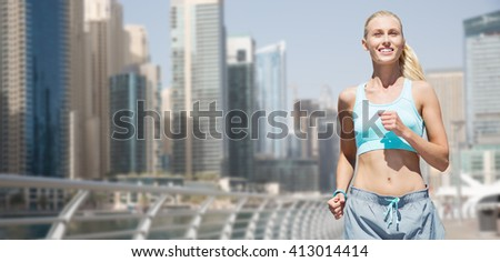 fitness, sport, friendship and healthy lifestyle concept - smiling young woman running or jogging over dubai city street background - stock photo