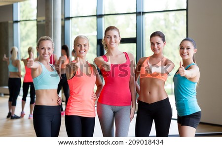 fitness, sport, friendship and lifestyle concept - group of women showing thumbs up gesture in gym - stock photo