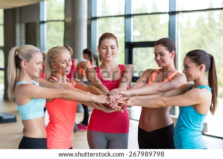 fitness, sport, friendship and lifestyle concept - group of women with hands on top of each other in gym - stock photo