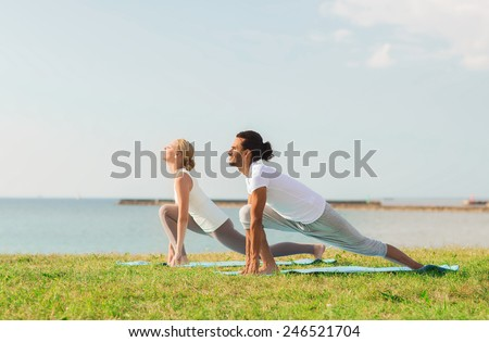 fitness, sport, friendship and lifestyle concept - smiling couple making yoga exercises on mats outdoors - stock photo