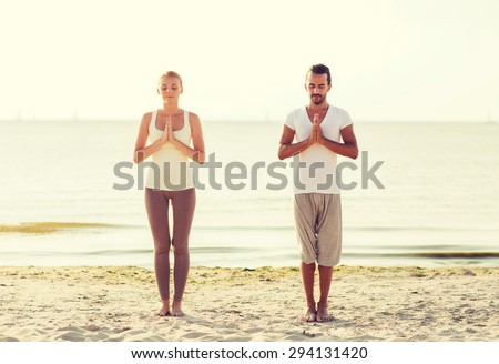 fitness, sport, friendship and lifestyle concept - smiling couple making yoga exercises on sand outdoors - stock photo