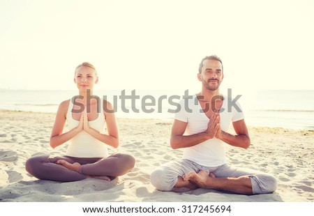 fitness, sport, friendship and lifestyle concept - smiling couple making yoga exercises sitting on sand outdoors - stock photo