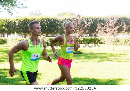 fitness, sport, friendship, race and healthy lifestyle concept - happy teenage friends or sportsmen couple running marathon with badge numbers outdoors - stock photo