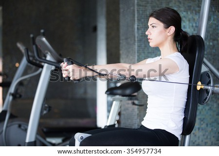 Fitness,sport lifestyle concept.Dedicated woman doing exercises with expander in gym.Fitness girl,execute exercise with gym apparatus,on triceps.Muscle toning and definition.Summer body goals - stock photo