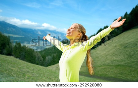 fitness, sport, people and emotions concept - happy woman in sportswear enjoying sun and freedom over mountains, green fields and blue sky background - stock photo