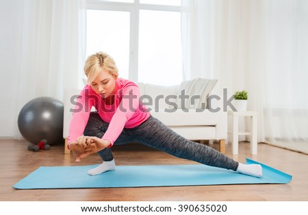 fitness, sport, people and healthy lifestyle concept - plus size woman stretching leg on mat at home