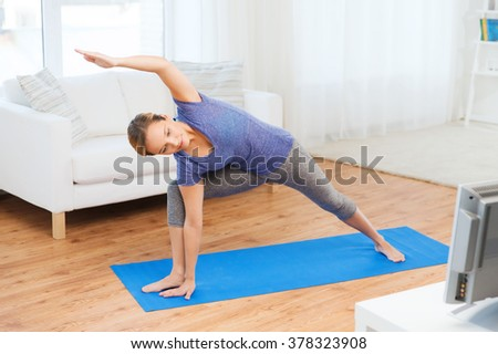 fitness, sport, people and healthy lifestyle concept - woman making yoga bikram triangle pose on mat and watching tv lesson - stock photo