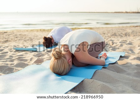 fitness, sport, people and lifestyle concept - close up of couple making yoga exercises on mats outdoors - stock photo