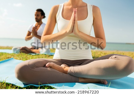 fitness, sport, people and lifestyle concept - close up of couple making yoga exercises sitting on mats outdoors - stock photo