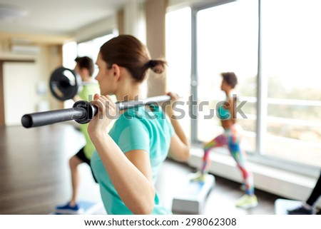 fitness, sport, people and lifestyle concept - close up of sportsmen exercising with bars and step platforms in gym - stock photo