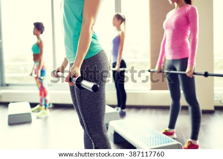 fitness, sport, people and lifestyle concept - close up of women exercising with bars and step platforms in gym - stock photo