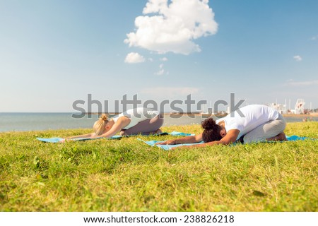 fitness, sport, people and lifestyle concept - couple making yoga exercises on mats outdoors - stock photo