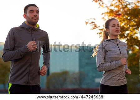 fitness, sport, people and lifestyle concept - couple running outdoors - stock photo
