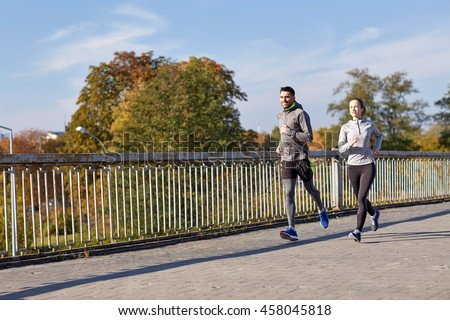 fitness, sport, people and lifestyle concept - happy couple running outdoors - stock photo
