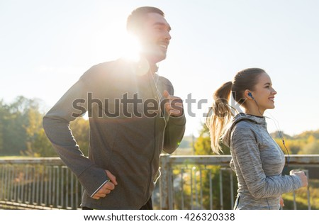 fitness, sport, people and lifestyle concept - happy couple with earphones running outdoors - stock photo