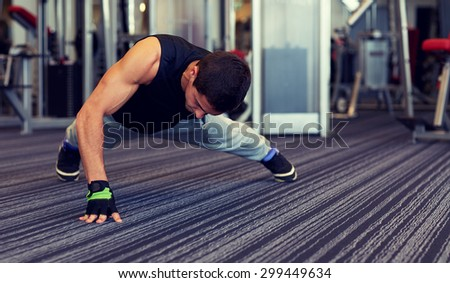 fitness, sport, people and lifestyle concept - man doing one arm push-ups in gym - stock photo