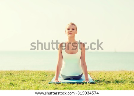 fitness, sport, people and lifestyle concept - young woman making yoga exercises lying mat outdoors