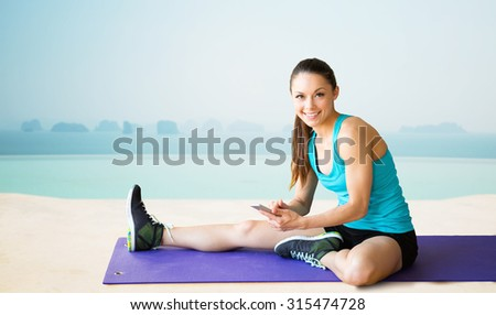 fitness, sport, people and technology concept - smiling woman with smartphone sitting on exercise mat over sea and pool at hotel resort background